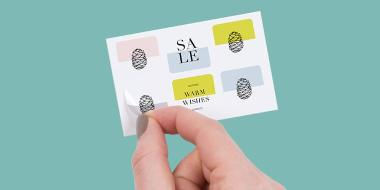 Hand removing a mini Sticker from a sheet of 6 small square Stickers