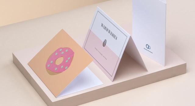 Greeting cards on a beige background including 1 orange donut card, 1 pink and white card and the back of a white card