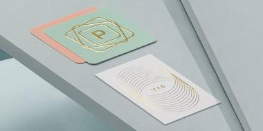 Gold foil business cards in various sizes, formats and designs on blue-grey background