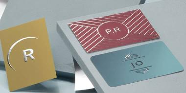 Silver foil business cards in various sizes, formats and designs on blue-gray background