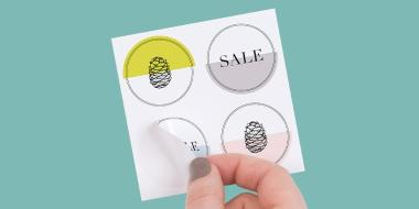 Hand removing a circular sticker from a sheet of 4 round stickers