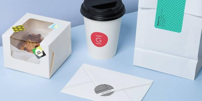 White pastry box, takeaway cup, envelope and paper pouch decorated with various colorful stickers on a light blue background