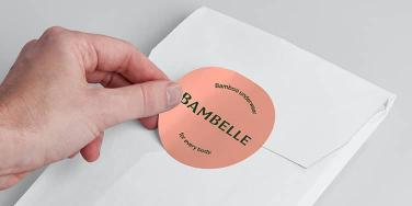 Hand putting a big pink round sticker on an envelope