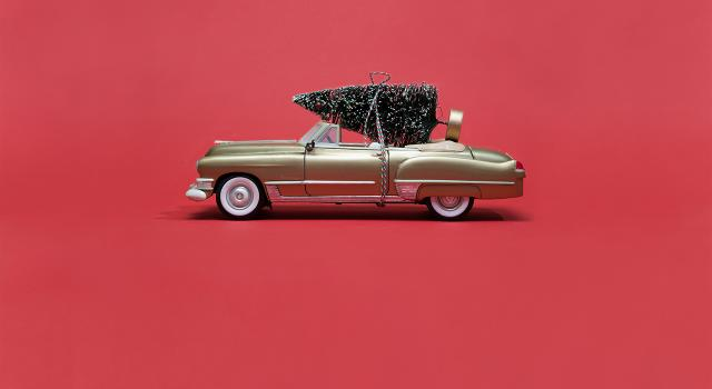 Golden convertible toy car with Christmas tree attached on top on red background for holiday season deliveries