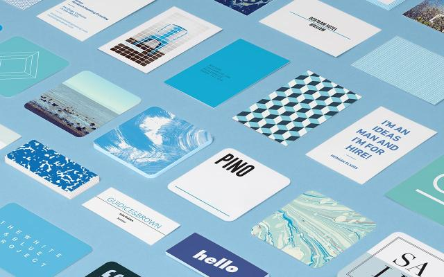 Mosaic of standard Business Cards in various sizes, shapes and designs on blue background.