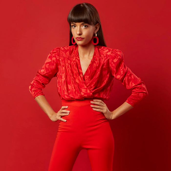 Jessica Walsh female graphic designer in red standing proud against a red background for a photoshoot