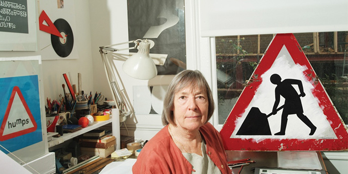 Margaret Calvert iconic female designer being photographed in front of her work for UK road signs