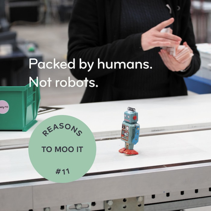 MOO worker in warehouse manually checking an order, little robot and text saying paxked by humans, not robots