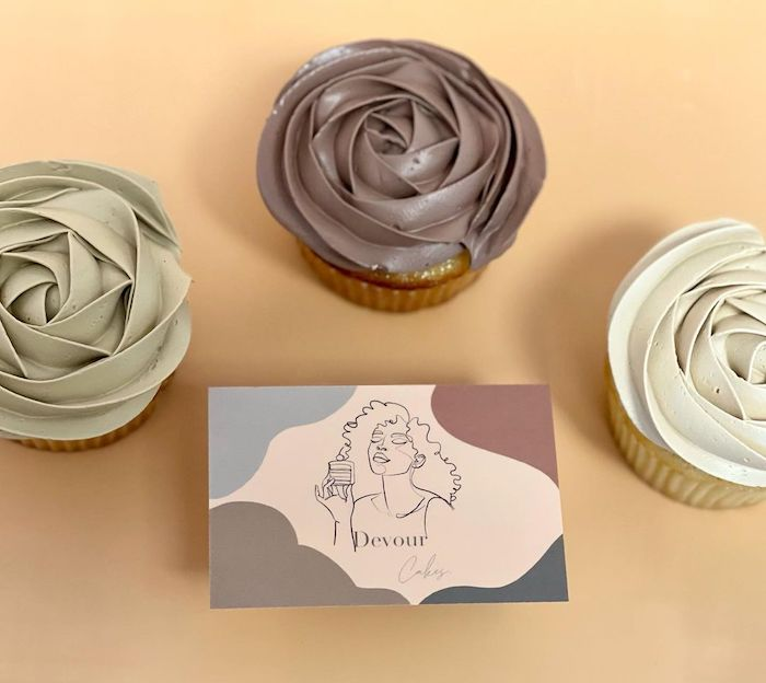 3 cupcakes and a Devour cake shop business card with muted colors and a line drawing of a curly haired woman eating a cake