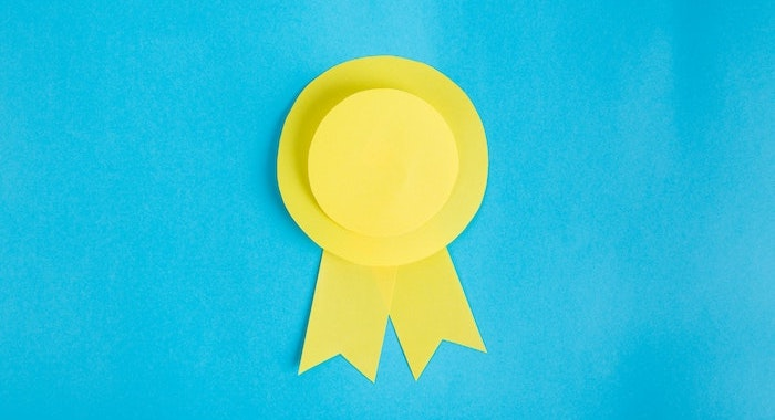 Yellow rosette made of paper on blue background