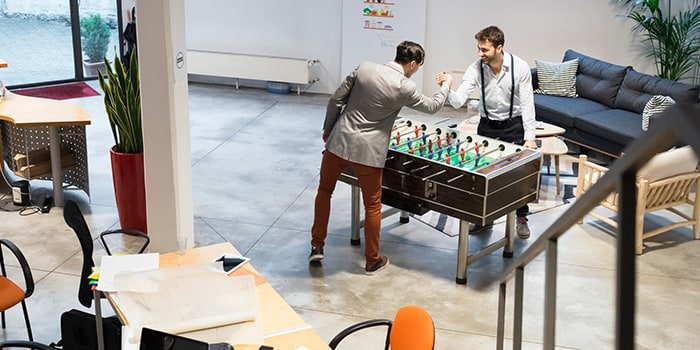 Two employees playing table football in the office