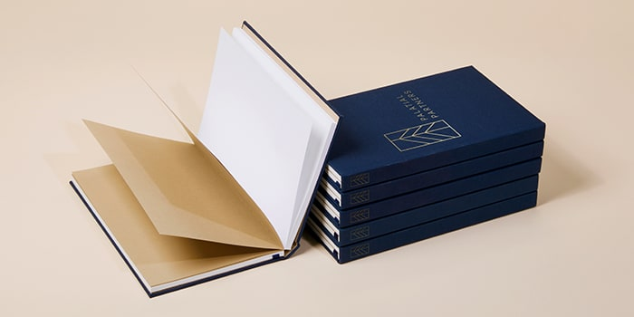 Open notebook next to a pile of five dark blue custom hardcover notebooks with a branded gold foil logo on the cover