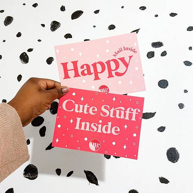 Hand holding one Happy postcard and one Cute Stuff Inside postcard by Hey Bre Creative Studio