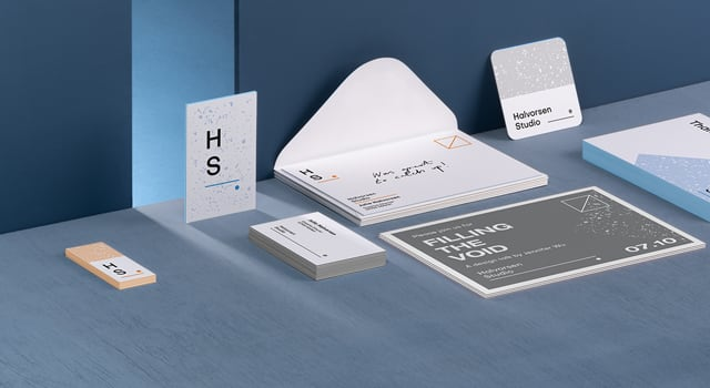 Set of Luxe printed products with thick, premium paper, including business cards, postcards and envelopes on blue background