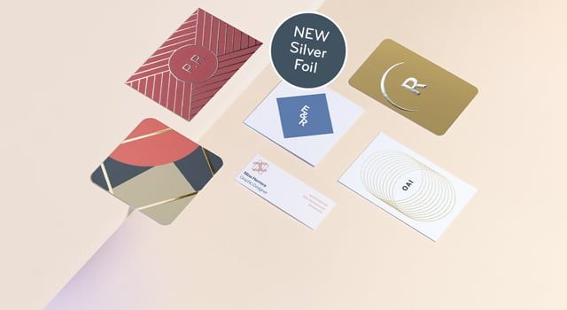 Business cards in various sizes, colours and designs on a beige background with a new silver foil tag