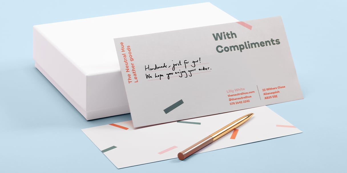 With compliments slip with personalised note and pen next to closed white box on light blue background