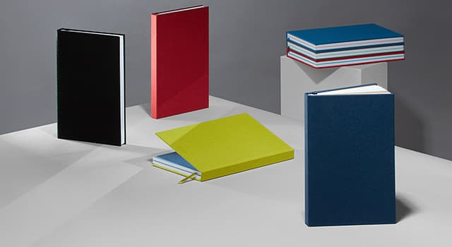 Set of colourful hardback Notebooks & soft cover Journals including 1 open Notebook with a coloured page and handwritten notes