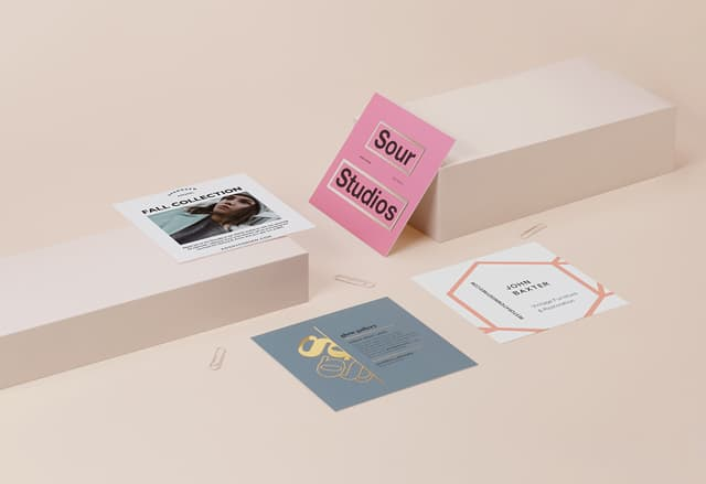 4 square postcards with full-color designs and special finishes on a cream-colored background with paperclips
